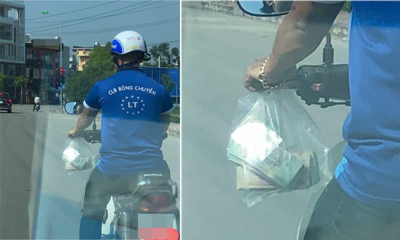 Tranh cãi chuyện người đàn ông để 2-3 cọc tiền trong túi bóng treo trước xe máy khi tham gia giao thông