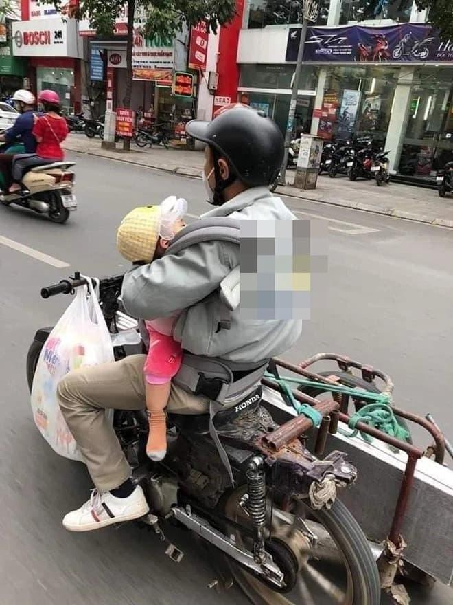 Hình ảnh ông bố chở đồ cồng kềnh trên phố, một tay ôm con trước ngực khiến ai nhìn cũng thương