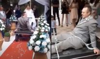 Chú rể bị cô dâu dùng xích trói tay chân kéo vào lễ đường khiến quan khách xôn xao