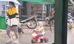 Người phụ nữ bị chỉ trích vô cảm khi thản nhiên che ô mặc em bé dầm mưa tầm tã