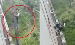 Đi tắt qua đường ray gặp đúng lúc tàu chạy, người đàn ông nhanh trí đu mình lên cột điện thoát chết trong gang tấc